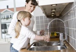 27462144 - small girl in the kitchen with her mother drinking water